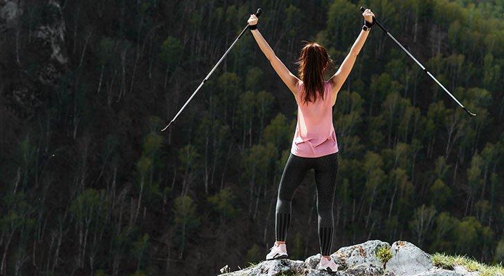 Hochmotivierte Nordic Walkerin auf dem Gipfel eines Berges
